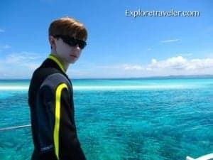 Bakasyon at Scuba Diving sa Coral Reefs ng Pilipinas - A person standing next to a body of water - Leisure